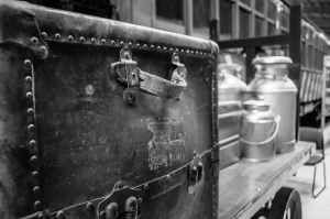 grayscale photography of travel case with milk churns on trailer